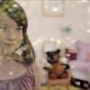 <h3>La petite fille regarde à travers la fenêtre de sa chambre, se demandant comment elle va annoncer à son ours en peluche la surprise qu'elle lui réserve… (vue de l'extérieur)</h3>